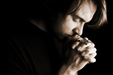 A man expresses his belief in God through prayer.
