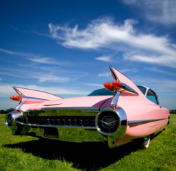 The tail fins of a 1959 pink Cadillac.