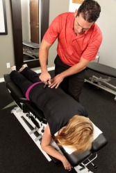 A chiropractor gives a woman an adjustment.
