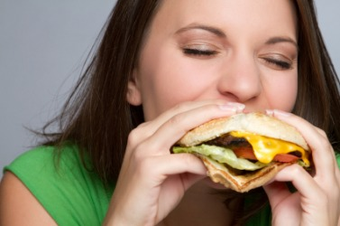A woman consumes a hamburger.