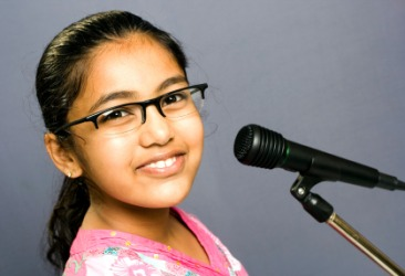 A girl about to speak into a microphone.