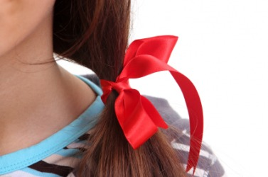 A girl with a red ribbon in her hair.