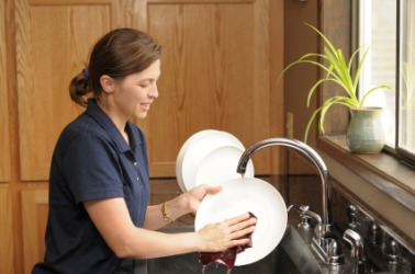 A woman rinses a plate.