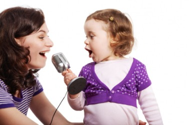 A llittle girl sings with her mother.