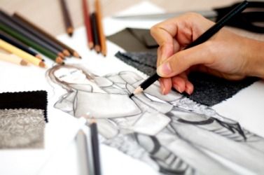 A fashion designer works on a sketch.