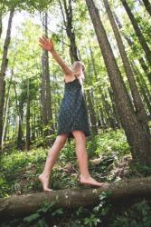 A girl walks tiptoe across a log.
