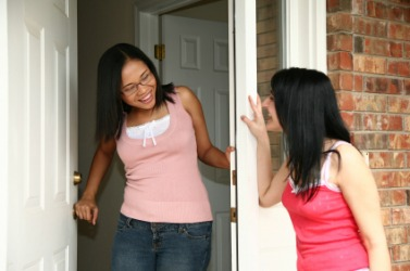A woman welcomes a visitor.