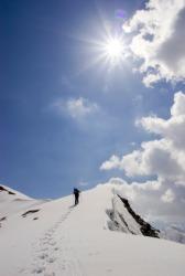 A hiker ascends a mountain ridge.