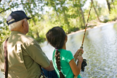 A grandfather imparts his knowledge of fishing to his granddaughter.