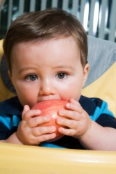 A child taking a bite out of an apple.