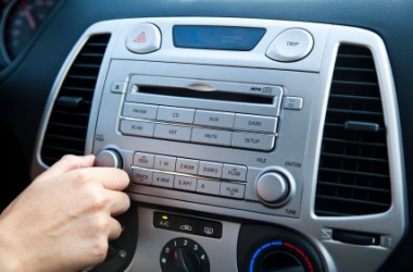A person adjusts the volume on their car radio.