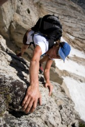 A woman endeavors to climb a mountain.
