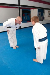 A martial arts student shows respect for his teacher.