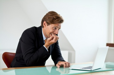 A man faces his computer task with trepidation.