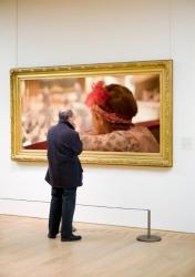A man scrutinizes a picture.
