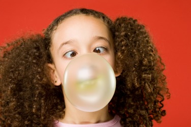 A little girl chewing bubble gum.