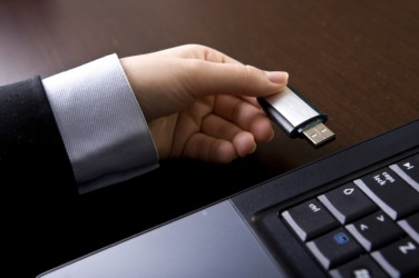A pen drive being inserted into a USB port.