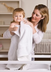 A mother drys her baby with a towel.