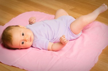 A baby laying on a pink blanket.