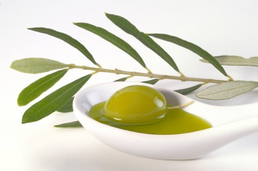 An olive rests in a spoon of extra-virgin olive oil.