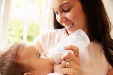 A mother pacifying a baby with a bottle.
