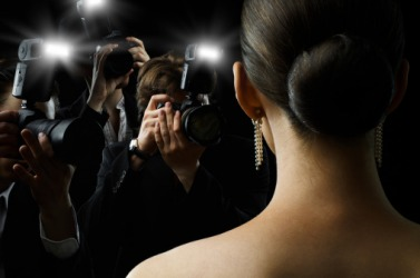 Paparazzi taking photographs of a celebrity.