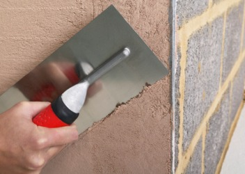 He will parge the wall with plaster in order to seal it from moisture.