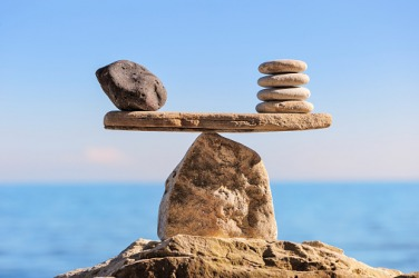 The parity of the rocks on each side of the balance allows it to remain level.