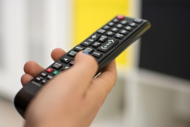 A person pressing the pause button on a remote control.