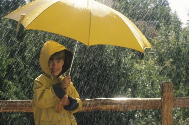 A boy with an umbrella standing in the pelting rain.