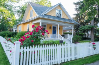 A white picket fence surrounds the perimeter of the house.