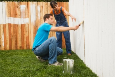The pernickety woman instructs her husband on the right way to paint a fence.