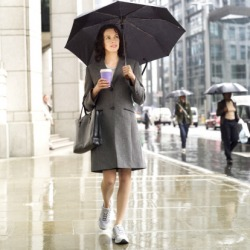 The persistent rain made walking to work a challenge because she had to carry her briefcase and coffee as well as an umbrella.