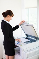 An employee making a copy on a photocopier.