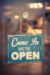 The placard on the front door lets customers know that the store is open for business.