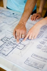 A couple pointing to blueprint plans.
