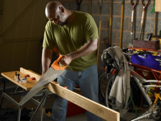 A man cutting a plank of wood with a saw.