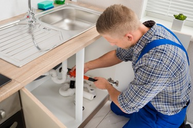 A plumber working on a kitchen sink.