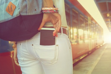 A woman putting a phone in the back pocket of her pants.
