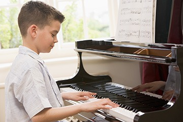 A young boy practising playing the piano.