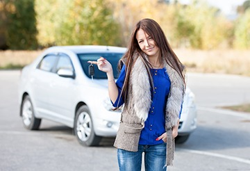 A young lady standing in front of her pre owned car.