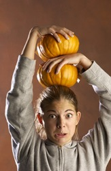 A girl balancing two pumpkins precariously on her head.
