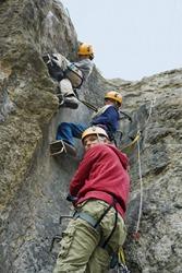 A family climbing a precipitous cliff.
