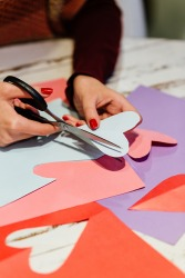Cutting construction paper hearts with precision using scissors.