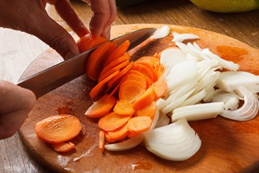 Cutting vegetables in preparation for making soup.