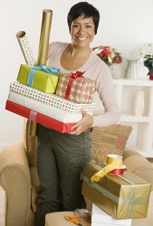 A woman holding several presents and gift wrap.