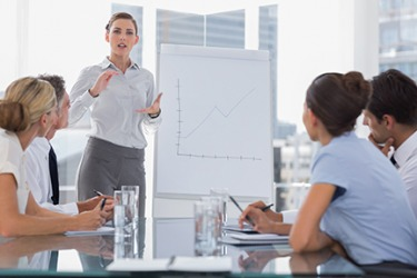 A woman giving a business presentation to her colleagues.