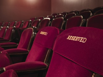 The first row of reserved chairs is the prime seating in a theater.