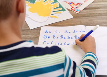 A school boy writing in print, practicing the alphabet.