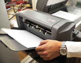 An office employee using a printer.